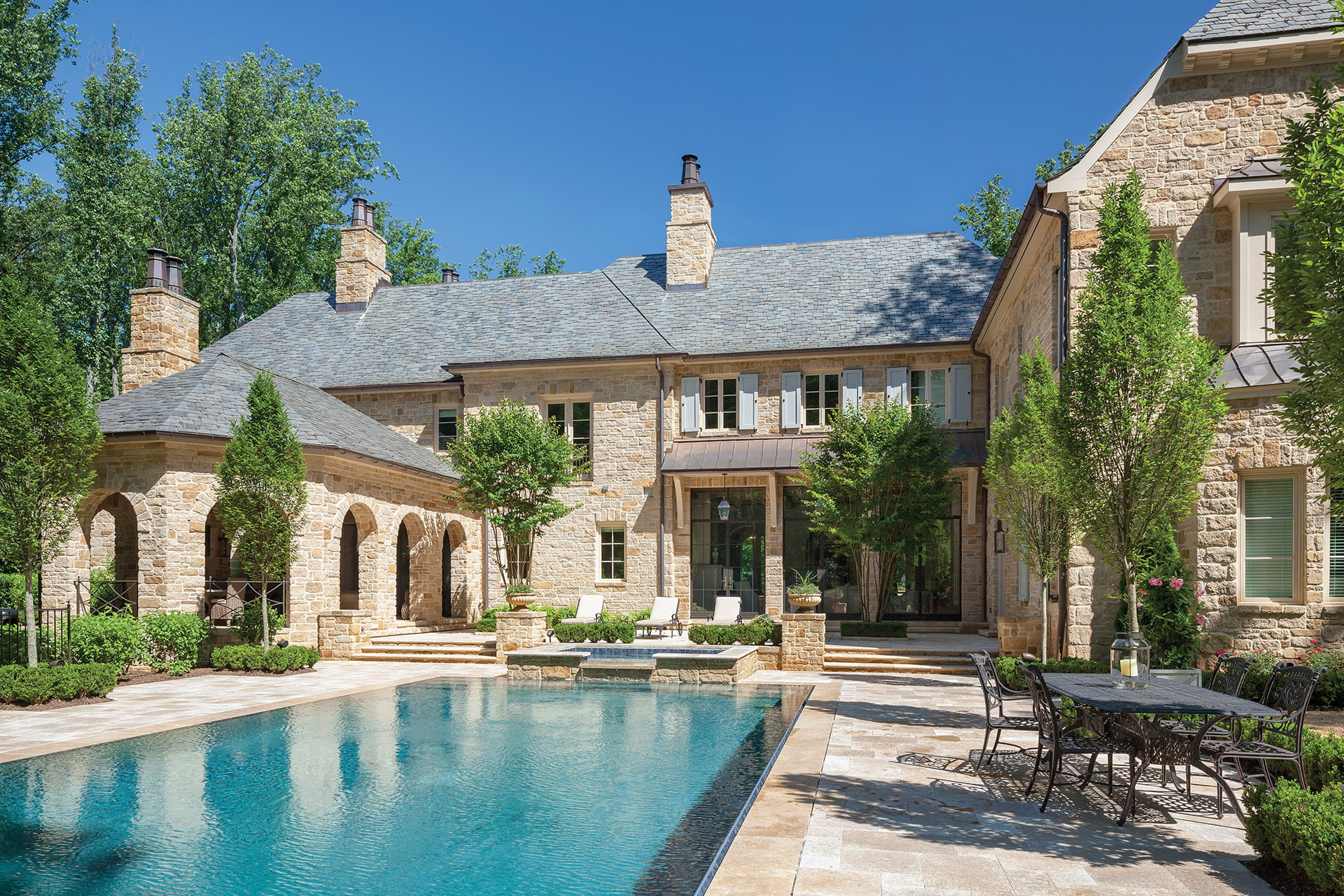 Travertine pool deck is enveloped by boxwood, crape myrtle and European hornbeam trees.