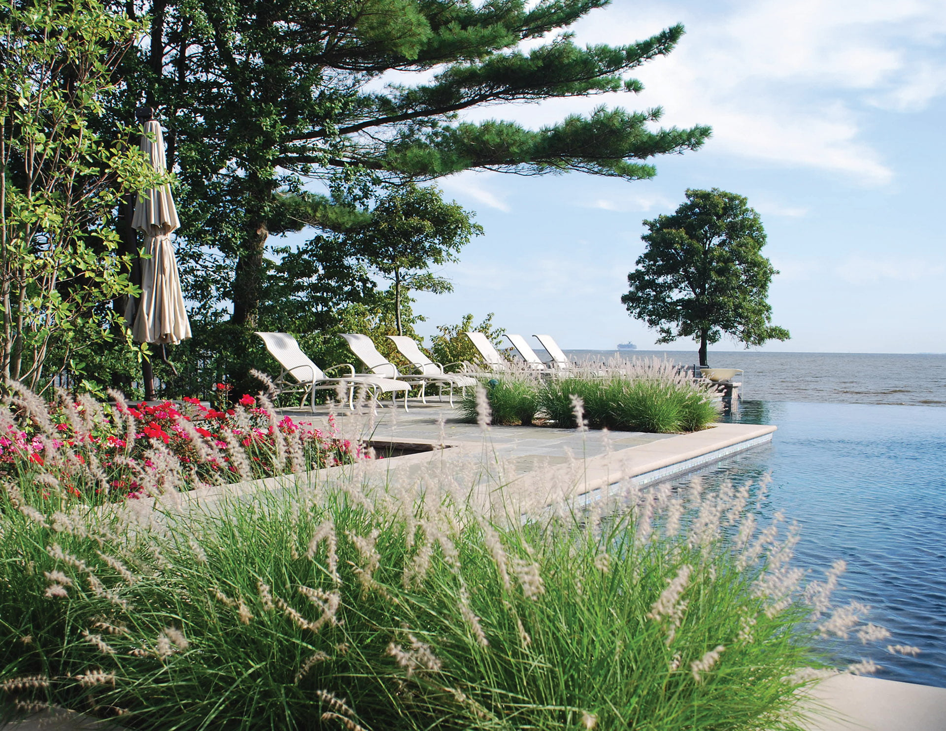 Raised-beam pool clad in natural stone veneer and Indiana limestone coping, designed by Walnut Hill Landscape Company