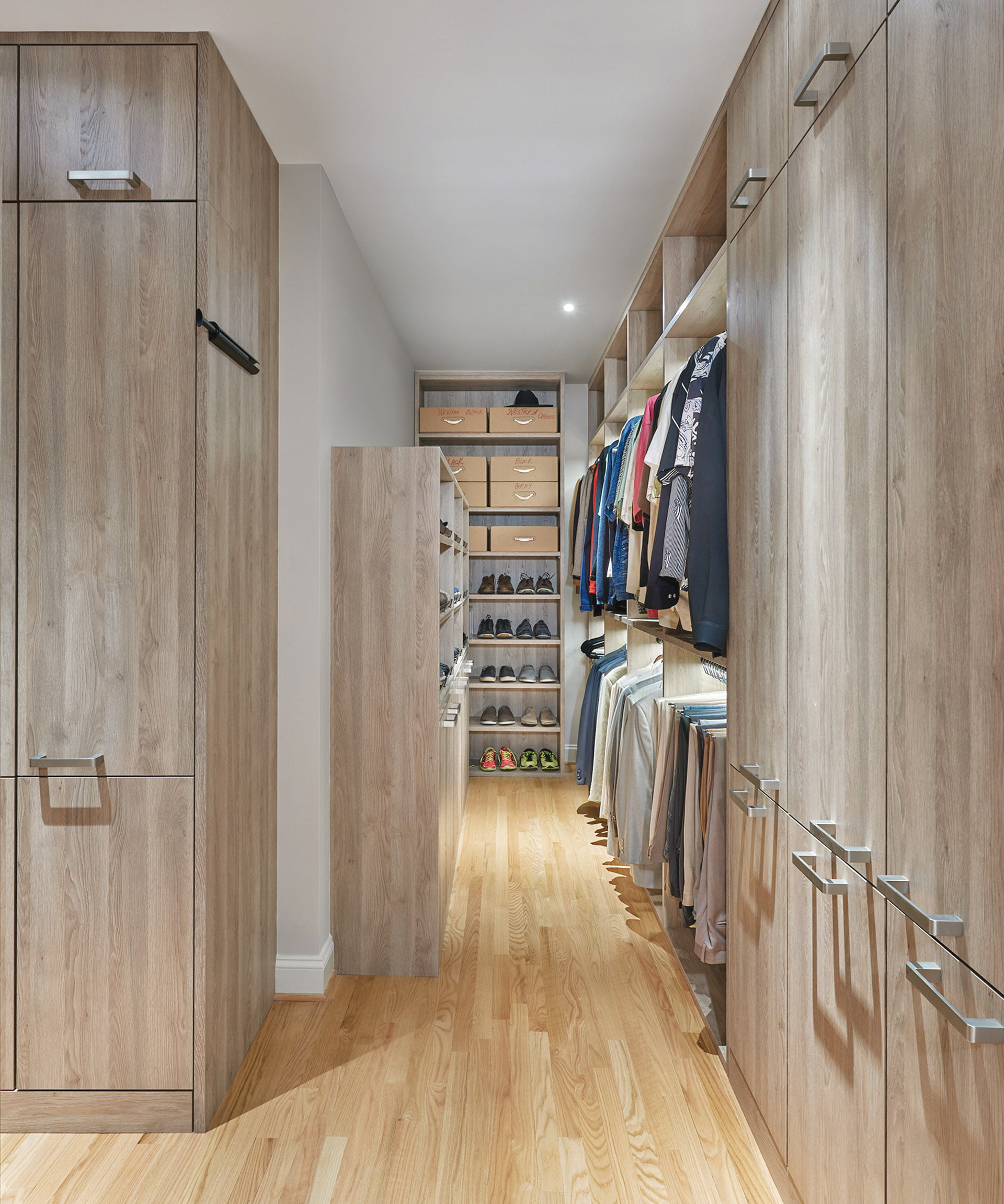 L-shaped closet stores shoes and clothing.