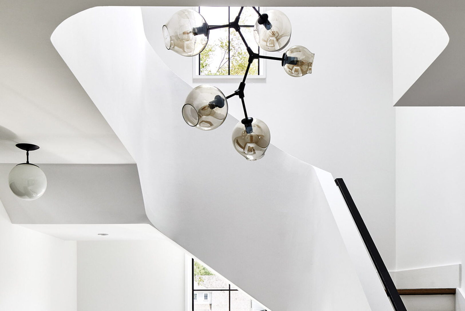Sculptural staircase with chandelier by France & Son