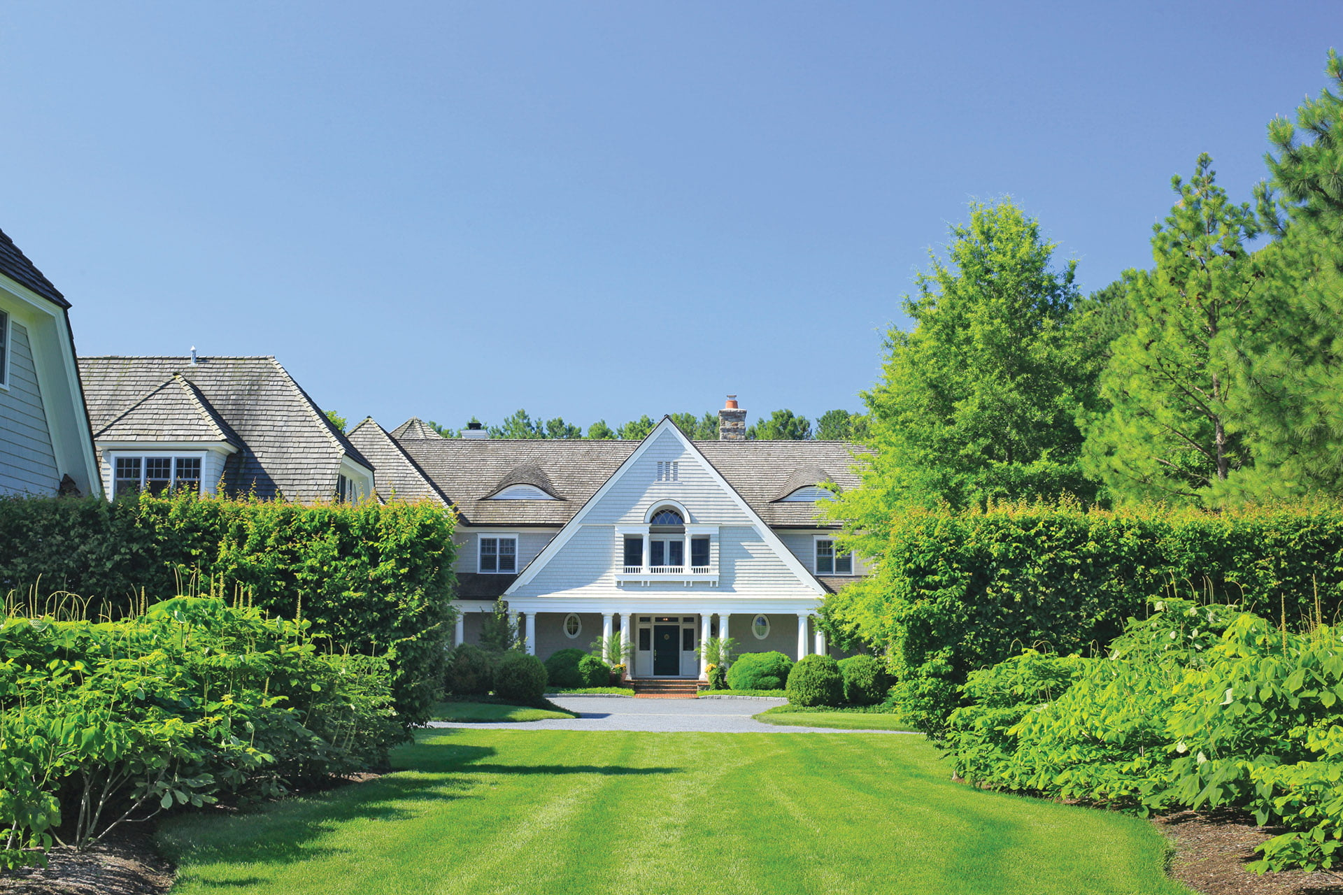 Parking court welcomes visitors to the Shingle-style house, designed by Grina-Lavie Architects.