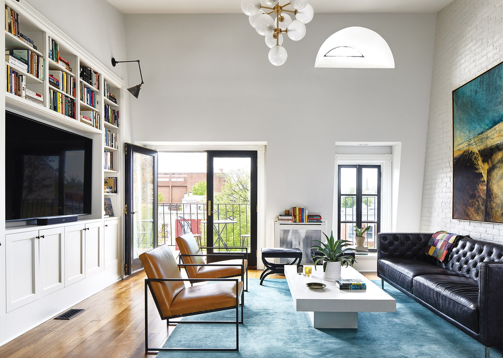 Vaulted ceiling, white-painted, exposed-brick wall and glass doors opening to a balcony.
