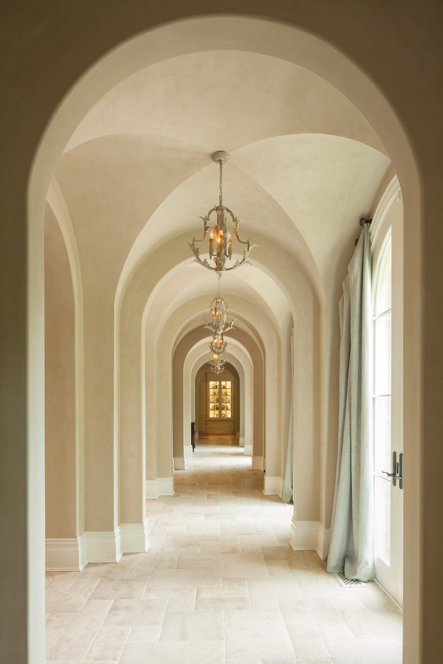 Acanthus leaf chandeliers by Aidan Gray light the dramatic groin-vaulted gallery