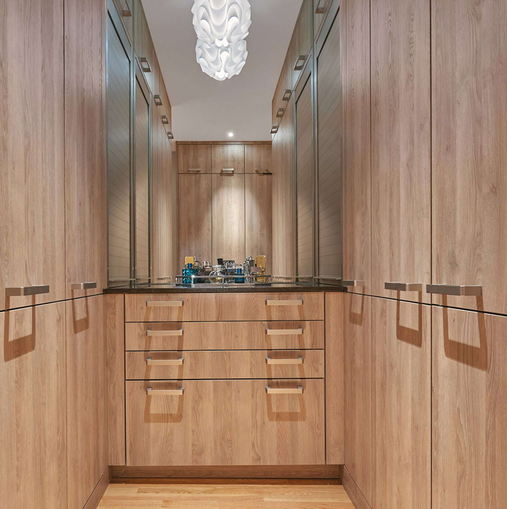 Chest of drawers in a closet is flanked by slatted-aluminum doors